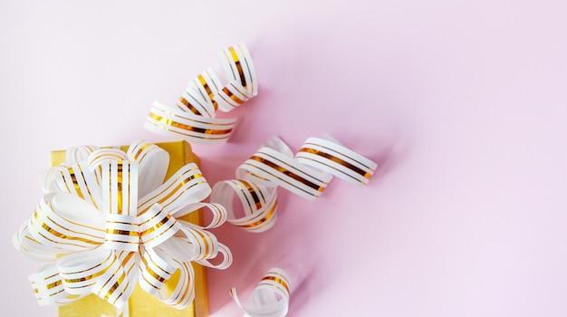 Confezione regalo avvolto in nastro a strisce bianche e oro su sfondo rosa pastello. copia spazio
