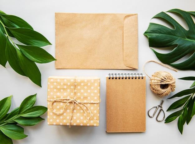 Confezione regalo, busta e quaderno con foglie verdi