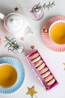 Confezione regalo con amaretti rosa tra tazze vintage di tè verde, stelle e piccoli vasi