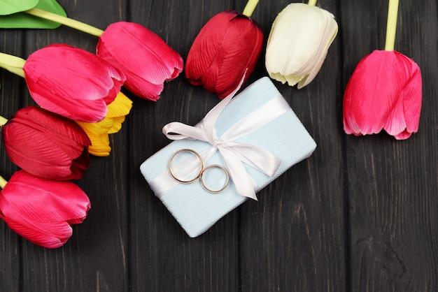 Confezione regalo con anelli d'oro con rosso con tulipani rossi per un matrimonio celebrazione san valentino 8 marzo