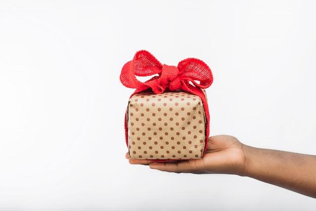 Confezione regalo con fiocco nelle mani di donna nera.
