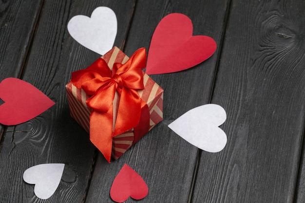 Confezione regalo con fiocco rosso e cuori di carta per san valentino