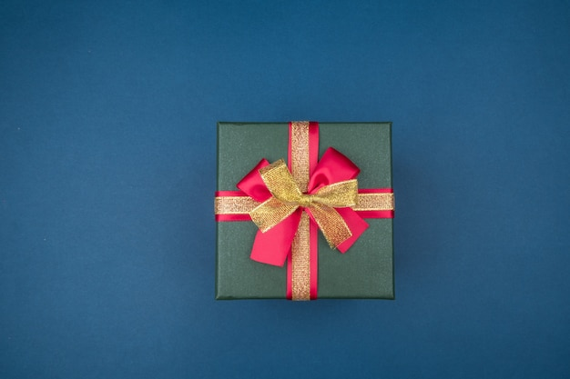 Confezione regalo con fiocco rosso e oro su sfondo blu scuro con stelle d'argento. concetto di vacanza.