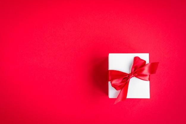 Confezione regalo con fiocco rosso su fondo rosso.