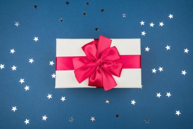 Confezione regalo con fiocco rosso su sfondo blu con stelle d'argento. concetto festivo