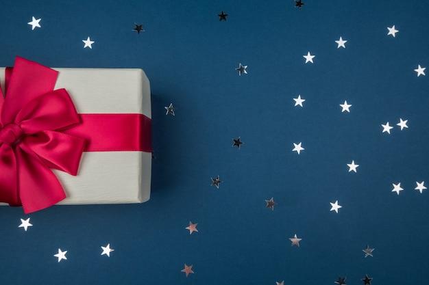 Confezione regalo con fiocco rosso su sfondo blu scuro con stelle d'argento. concetto di vacanza
