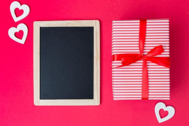 Confezione regalo con lavagna e cuori chiari sul tavolo