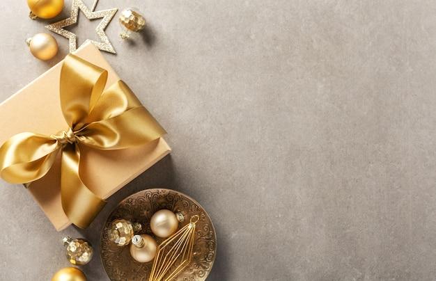 Confezione regalo con nastro dorato su grigio