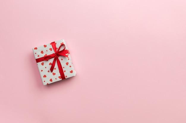 Confezione regalo con nastro rosso e cuore rosa