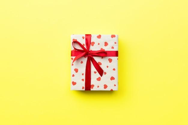 Confezione regalo con nastro rosso e cuore su sfondo giallo, vista dall'alto con lo spazio della copia per il testo
