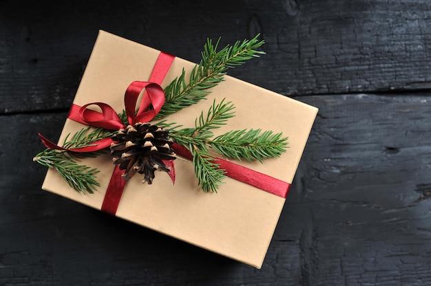 Confezione regalo con nastro rosso, ramo di abete e cono