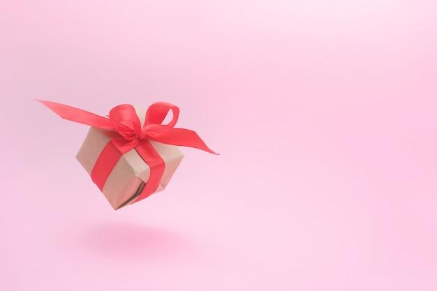 Confezione regalo con nastro rosso sul rosa.