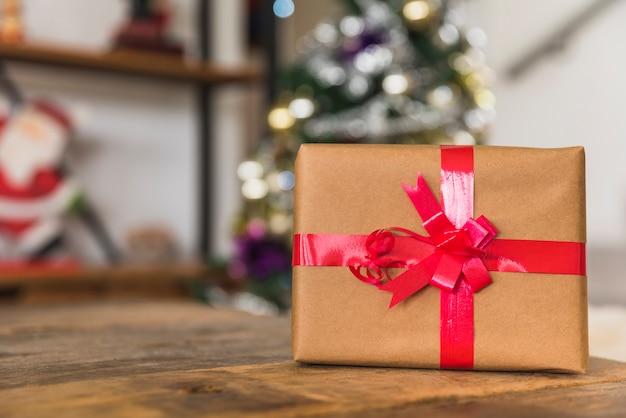 Confezione regalo con nastro rosso sul tavolo