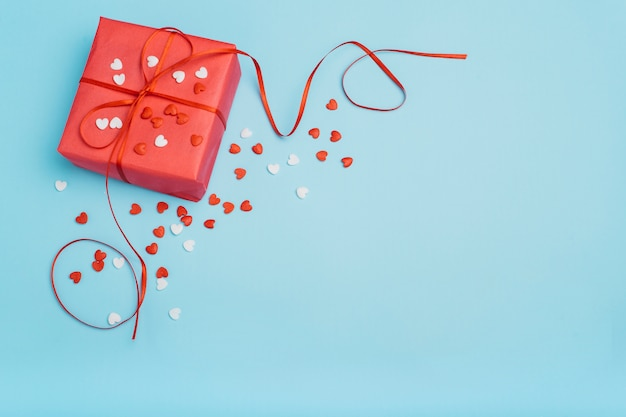 Confezione regalo con piccoli cuori sul tavolo blu