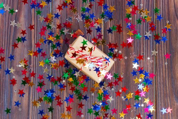 Confezione regalo con stella. creativo con decorazioni festive su sfondo nero. stelle di coriandoli, rosse, gialle con scatola regalo. esplosione di coriandoli