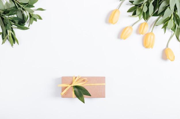 Confezione regalo con un nastro giallo sul tavolo vicino ai tulipani