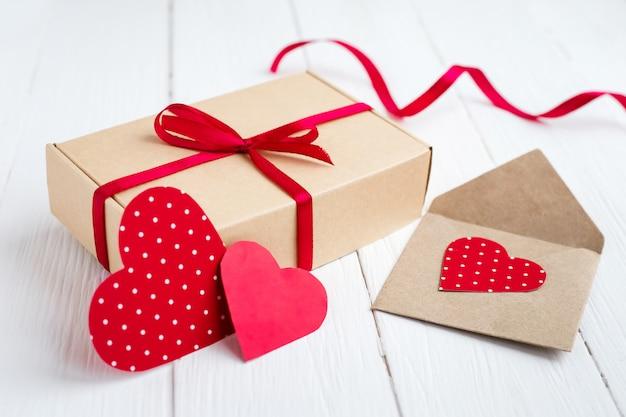 Confezione regalo con un nastro rosso, due cuori rossi, lettera d'amore su un fondo di legno bianco