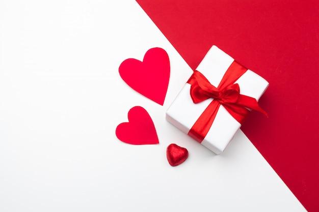 Confezione regalo, cuori di carta rossa. san valentino. forma del focolare. copia spazio, disteso