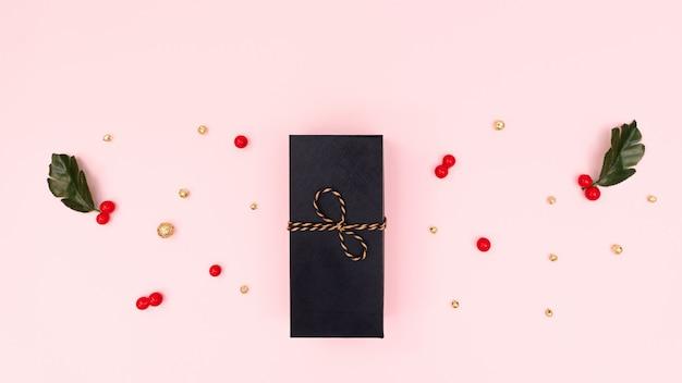 Confezione regalo di natale, ciliegia rossa e decorazioni dorate. natale, concetto di capodanno. vista piana, vista dall'alto, copia spazio