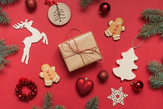 Confezione regalo di natale, decorazioni fai-da-te in legno, rami sempreverdi, biscotti di panpepato.