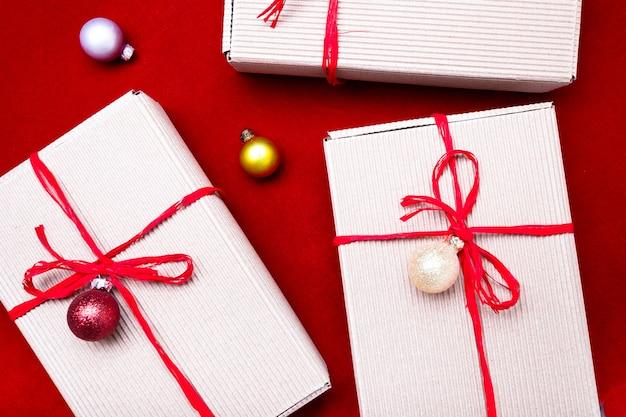 Confezione regalo di natale. regali di natale in scatole artigianali e nastro rosso su sfondo rosso. piatto disteso con copyspace. stile piatto laico. vista dall'alto.