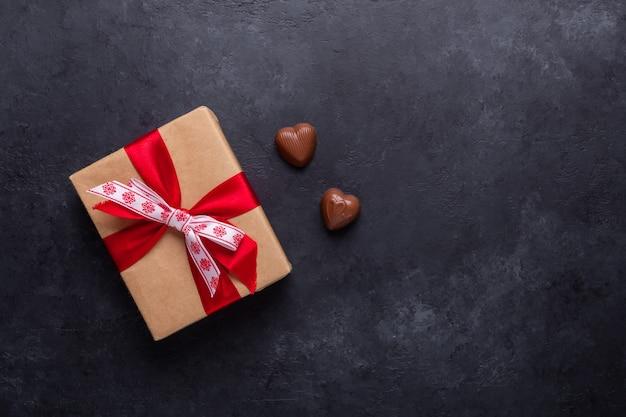Confezione regalo, dolci al cioccolato su pietra nera. copyspace della cartolina d'auguri di san valentino