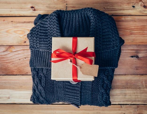 Confezione regalo e abbigliamento su fondo in legno per regalo di natale.