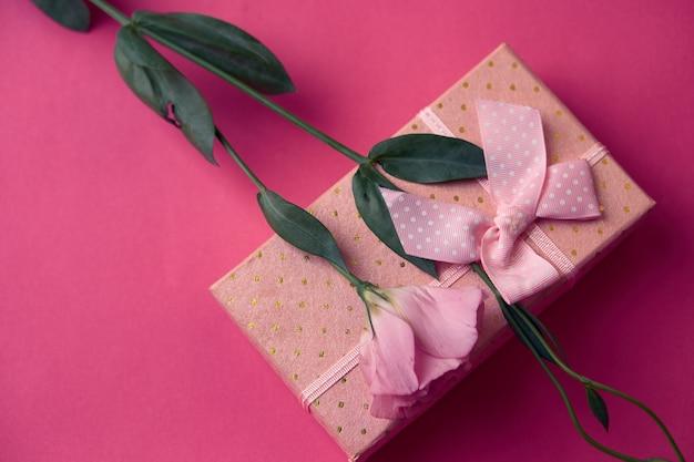 Confezione regalo e bouquet di fiori in vacanza con fiocco rosa