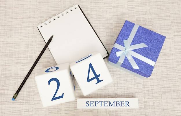 Confezione regalo e calendario in legno con numeri blu alla moda, 24 settembre