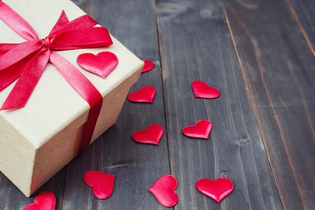 Confezione regalo e cuore rosso su sfondo di tavolo in legno con spazio di copia,