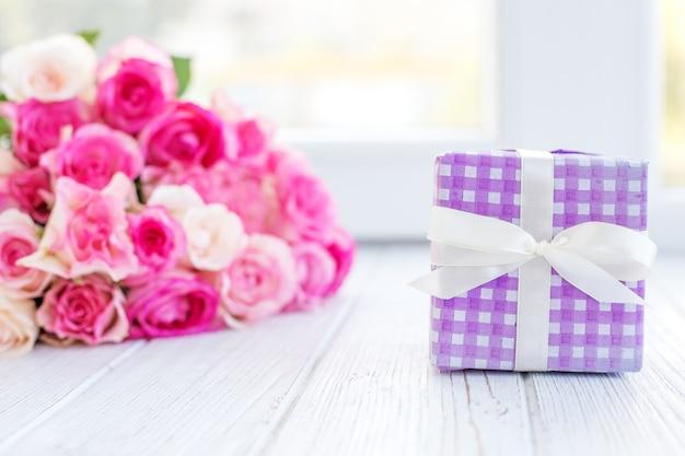 Confezione regalo e un mazzo di fiori. il concetto è una vacanza, valen