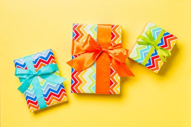 Confezione regalo fiocco blu, verde e arancione per natale o il giorno in giallo, vista dall'alto