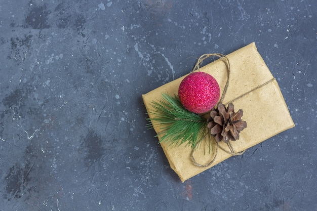 Confezione regalo in carta kraft con decorazioni natalizie su sfondo scuro