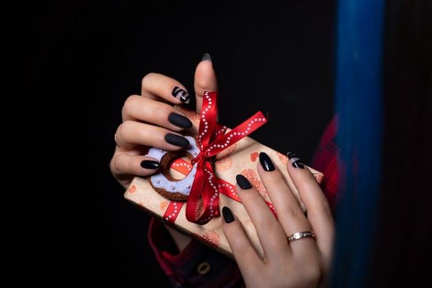 Confezione regalo in carta kraft fasciata da un nastro decorato con una ciambella in tessuto