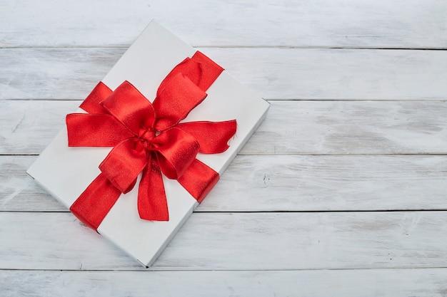 Confezione regalo in colore bianco con nastro rosso, regalo di compleanno, vista dall'alto