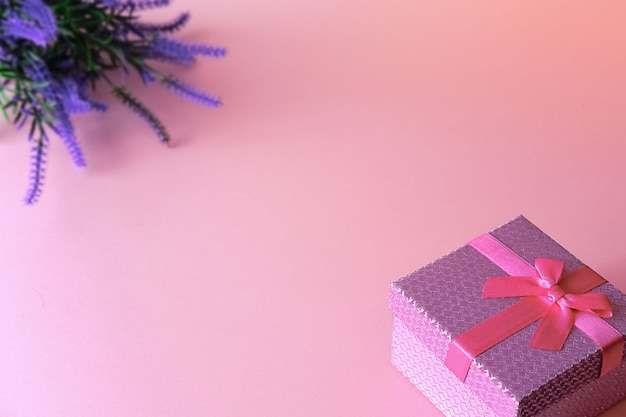 Confezione regalo legata con un nastro con bouquet di fiori di campo viola