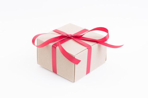 Confezione regalo marrone con nastro rosso su bianco