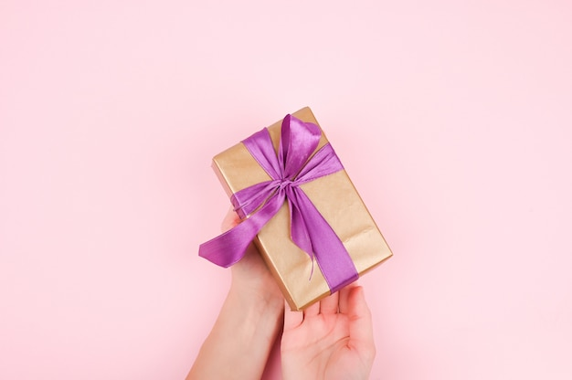 Confezione regalo nelle mani di una ragazza, vista dall'alto. disteso su sfondo rosa, donna fa un regalo per natale o compleanno