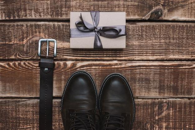 Confezione regalo per la festa del papà con accessori da uomo cintura e scarpe di cuoio su un tavolo di legno. disteso.