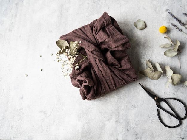 Confezione regalo riutilizzabile in tessuto ecologico con eucalipto e fiori bianchi. alternativa di confezione regalo riutilizzabile e romantica. concetto di rifiuti zero.