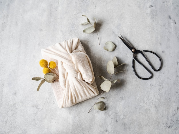 Confezione regalo riutilizzabile in tessuto ecologico con eucalipto e fiori gialli. alternativa di confezione regalo riutilizzabile e romantica.