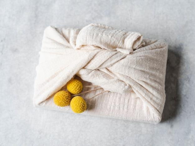 Confezione regalo riutilizzabile in tessuto ecologico con fiori gialli secchi. alternativa di confezione regalo riutilizzabile e romantica. concetto di rifiuti zero. vista dall'alto