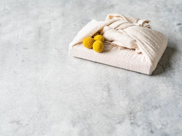 Confezione regalo riutilizzabile in tessuto ecologico con fiori gialli secchi. alternativa di confezione regalo riutilizzabile e romantica. concetto di rifiuti zero.