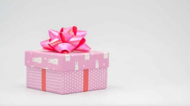 Confezione regalo rosa con nastro rosa su sfondo bianco congratulazioni in varie occasioni - immagini