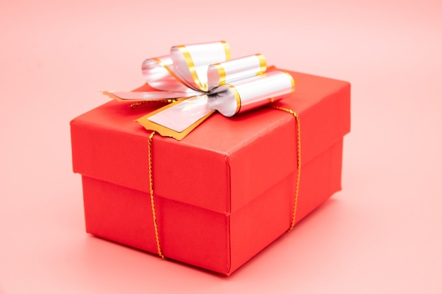 Confezione regalo rossa con nastro bianco e regali su sfondo rosa.