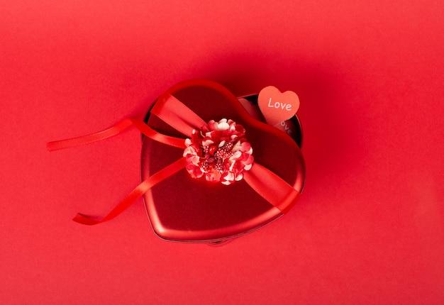 Confezione regalo rossa e un cuore di carta fatta a mano