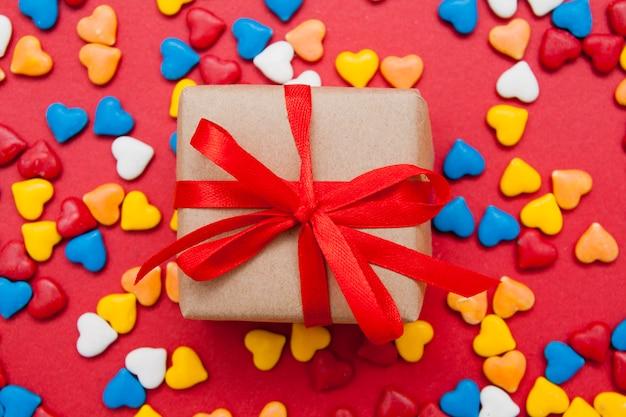 Confezione regalo su una superficie rossa con cuori colorati