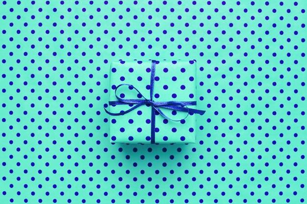 Confezione regalo turchese su sfondo blu con pois