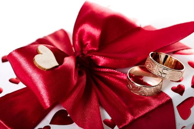 Confezione regalo, una scatola con una sorpresa per la festa, avvolta in carta bianca con cuori rossi