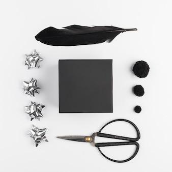 Confezione regalo vicino a fiocchi decorativi, piume e forbici